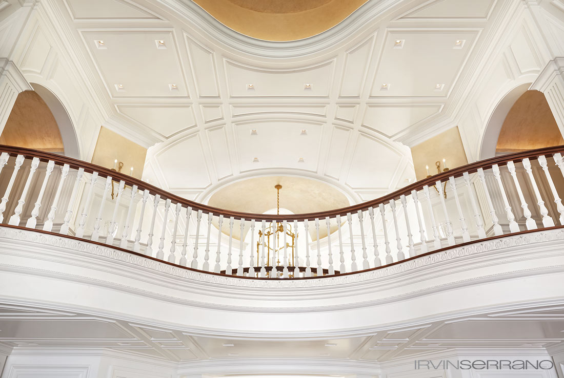 View from below of curved, intricate molding, trim and paneling of a upstairs hallway, crafted by Tidewater Millwork, in a Southport estate in Maine.
