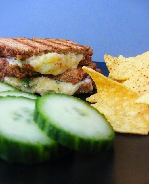 Comfort Cheese Toastie with cheese oozing out, on black plate with cucumber and crisps