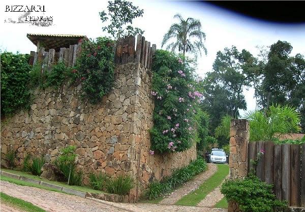 Vista da rua para a residência, o muro de arrimo com pedra. No topo do muro fixamos os dormentes de madeira e em baixo o calçamento de pedra até a residência nesse condomínio em Atibaia-SP.