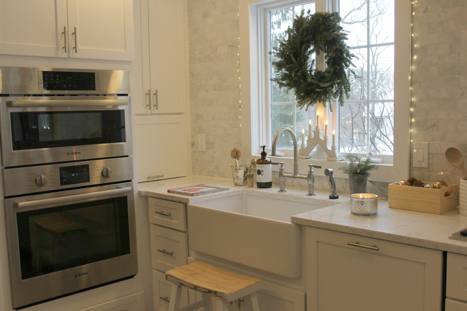 My white modern farmhouse kitchen with wreath over farm sink - Hello Lovely Studio