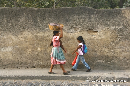 Woman holding a wicker basket on her head walks past a young girl.