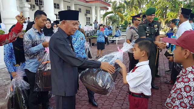 Plt Bupati Asahan Surya memberikan bingkisan pada murid berprestasi.