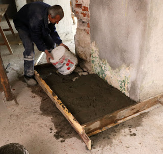 A bucket of concrete is added to the step