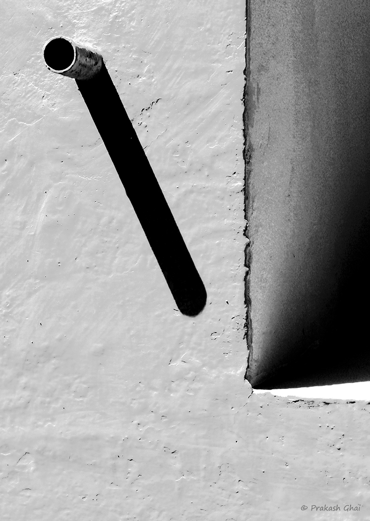 A Minimalist Photo of Elongated shadow of drainage pipe supported by a vertical rectangle