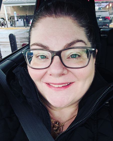 image of me from the shoulders up, in the car, wearing glasses and a big black winter coat, with my hair pulled back and smiling