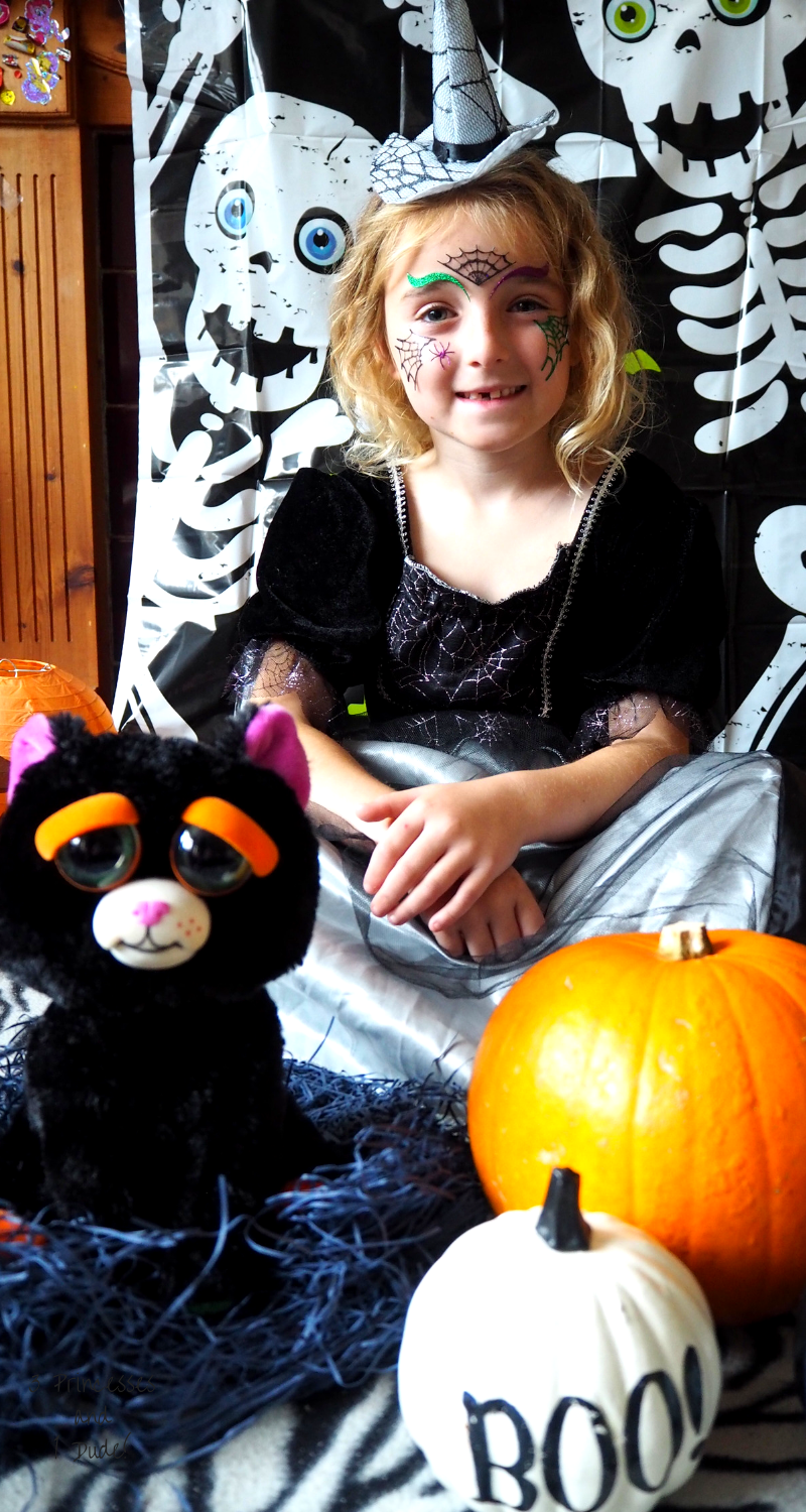 A young girl in a black and silver witch costume is sat smiling with Feisty Pet Cranky Cathy, a 25cm soft toy, the toy is black with big doe eyes, cartoonish orange eyebrows, and a white mouth.