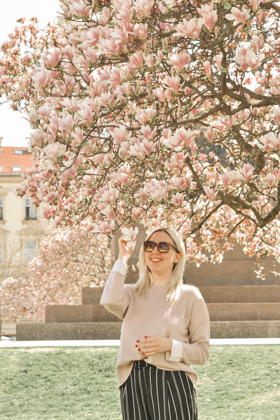Fashion blogger stating under a magnolia tree in a light pink sweater