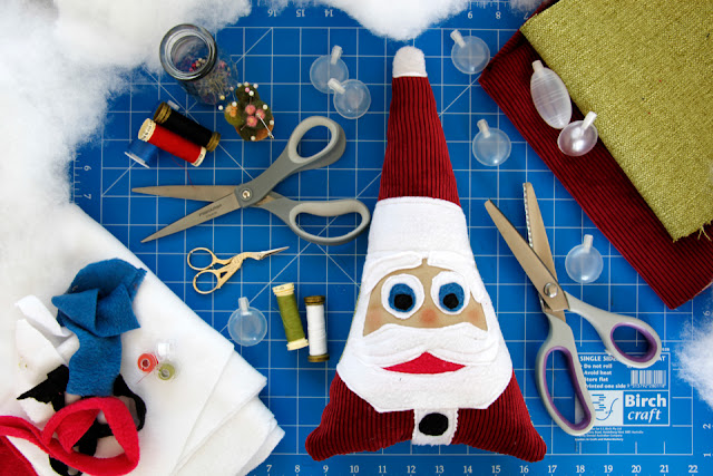 Homemade Christmas Santa dog toy on a craft mat with sewing supplies