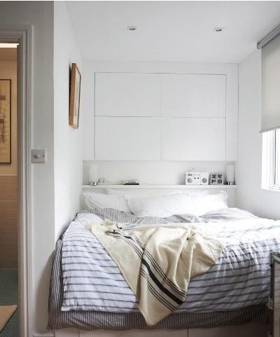 Jika headboard saja dianggap tidak cukup, gunakan juga seluruh dinding di belakang ranjang sebagai ruang penyimpanan, dengan cara memasang rak atau lemari.