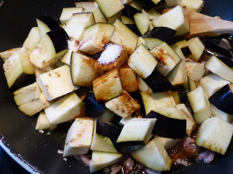 Ajoutez les aubergines, les sauces soja, l'eau et le sucre.