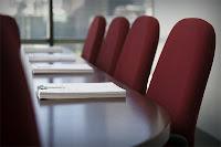 Bir toplantı masası etrafındaki boş koltuklar
