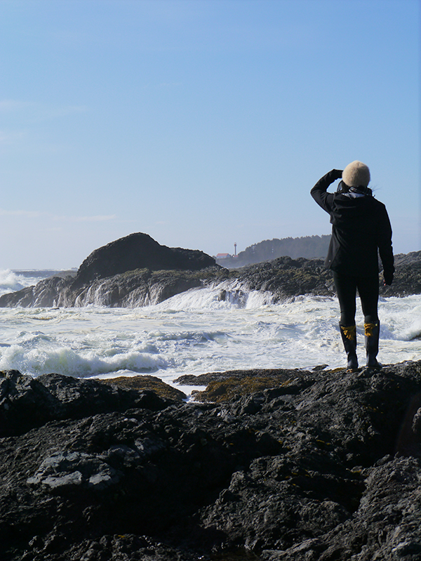 Vancouver beauty, life, and style blogger Solo Lisa stares at the waves breaking on the rocks in Tofino, BC, Canada