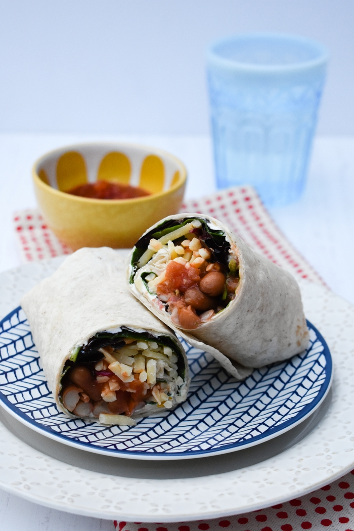 a Spicy Bean Lunch Wrap on a spotty napkin with a bowl of salsa