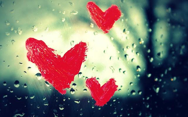 Geverfde rode hartjes op een raam met regendruppels