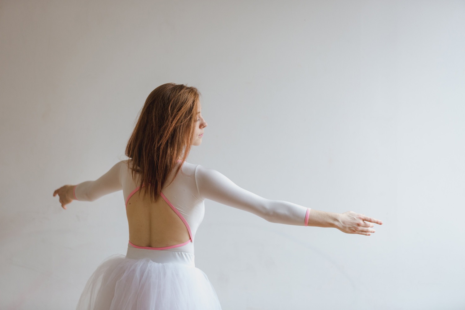 woman dancing ballet in a leotard and tutu skirt with her arms open