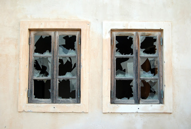 A pair of broken windows in a white wall.