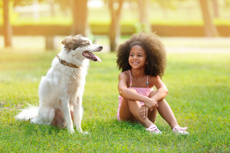 A girl and her dog sit together on the grass. Pets are good for children - read more about the benefits.