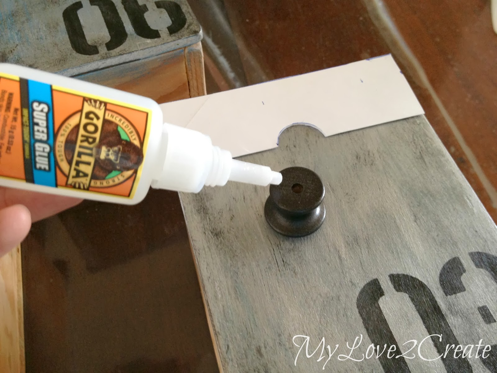 adding super glue to back of drawer knob to attach it to drawer front