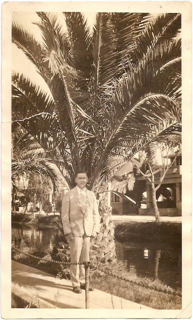 Leo Harrington standing in front of palm tree near canal or waterway