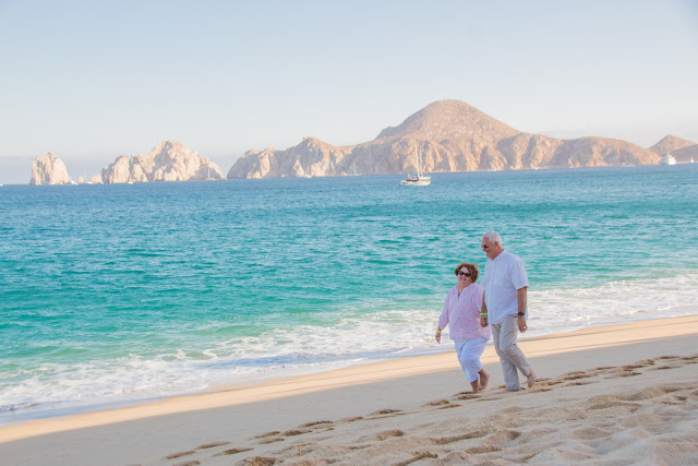 husband and wife walking on the beach in Cabo San Lucas