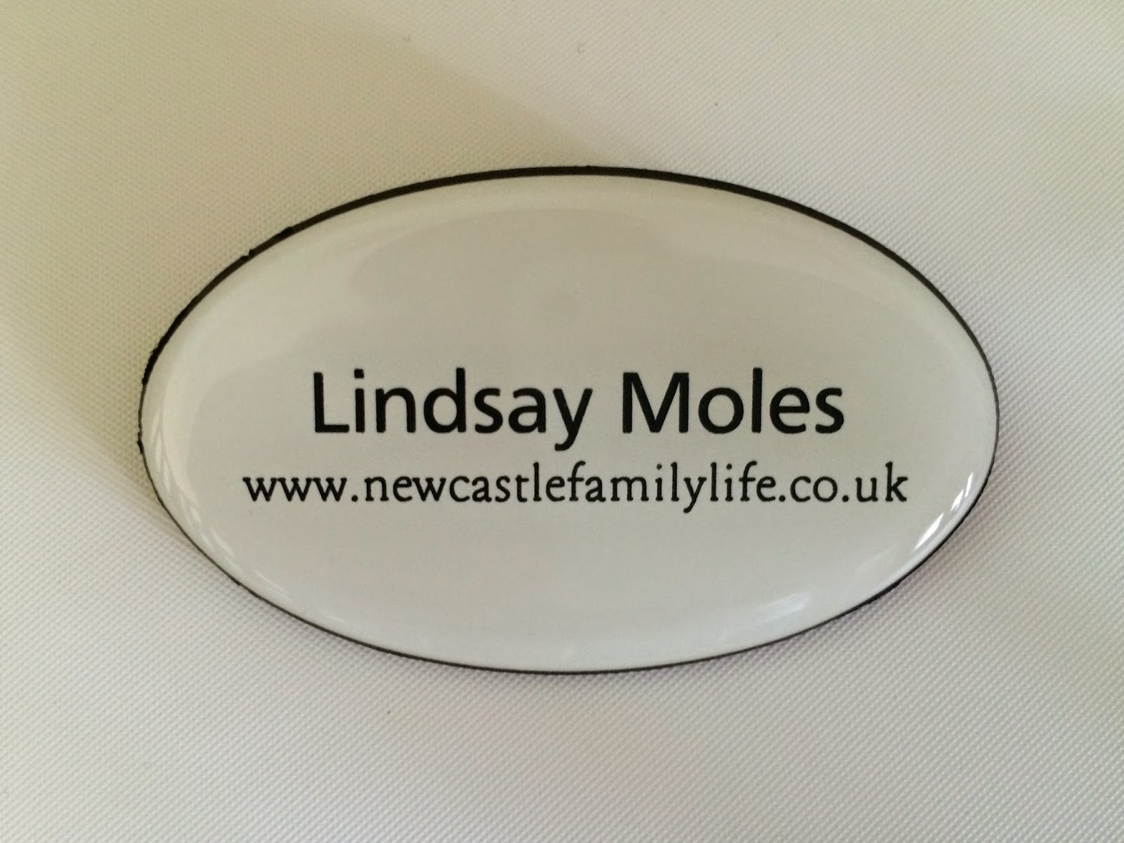 white oval name badge