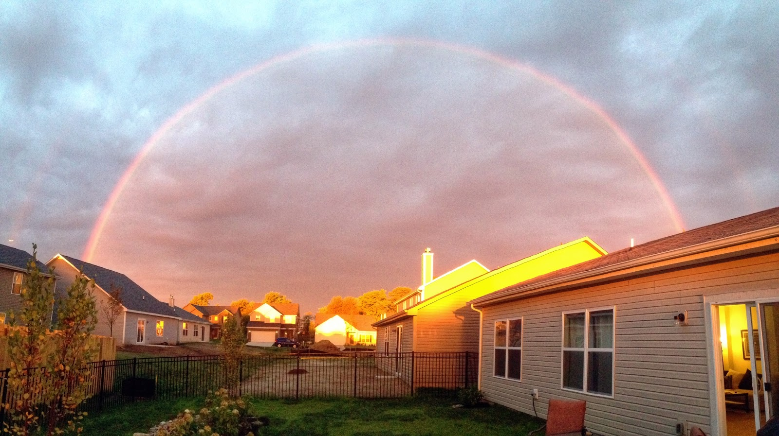 full rainbow over house with pink middle