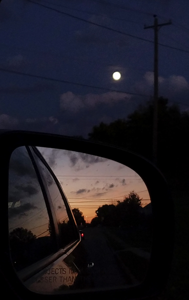 image of a full moon in a darkening sky, taken out a car window, with the setting sun captured in a rear-facing mirror