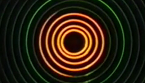 Concentric neon thin circles on a black background. Still from a John Whitney video, adapted for use with switch users.