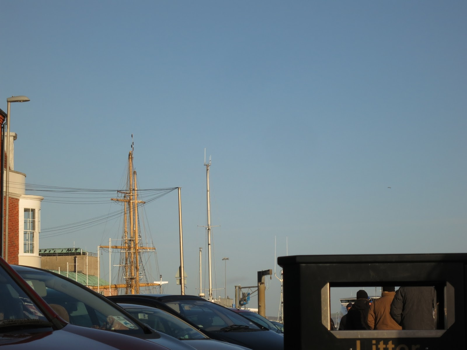 Cars, a tall ship, a black street bin with people seen through the opening.