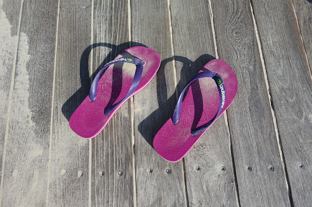Pink and purple havaianas covered with sand on a wooden boardwalk dusted with sand