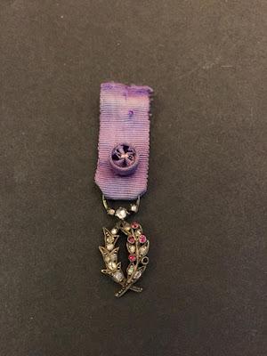 Palme d'officier d'Académie, modèle miniature en argent travaillé à jours, enrichi de brillants et de grenats, ruban à rosette (collection particulière)