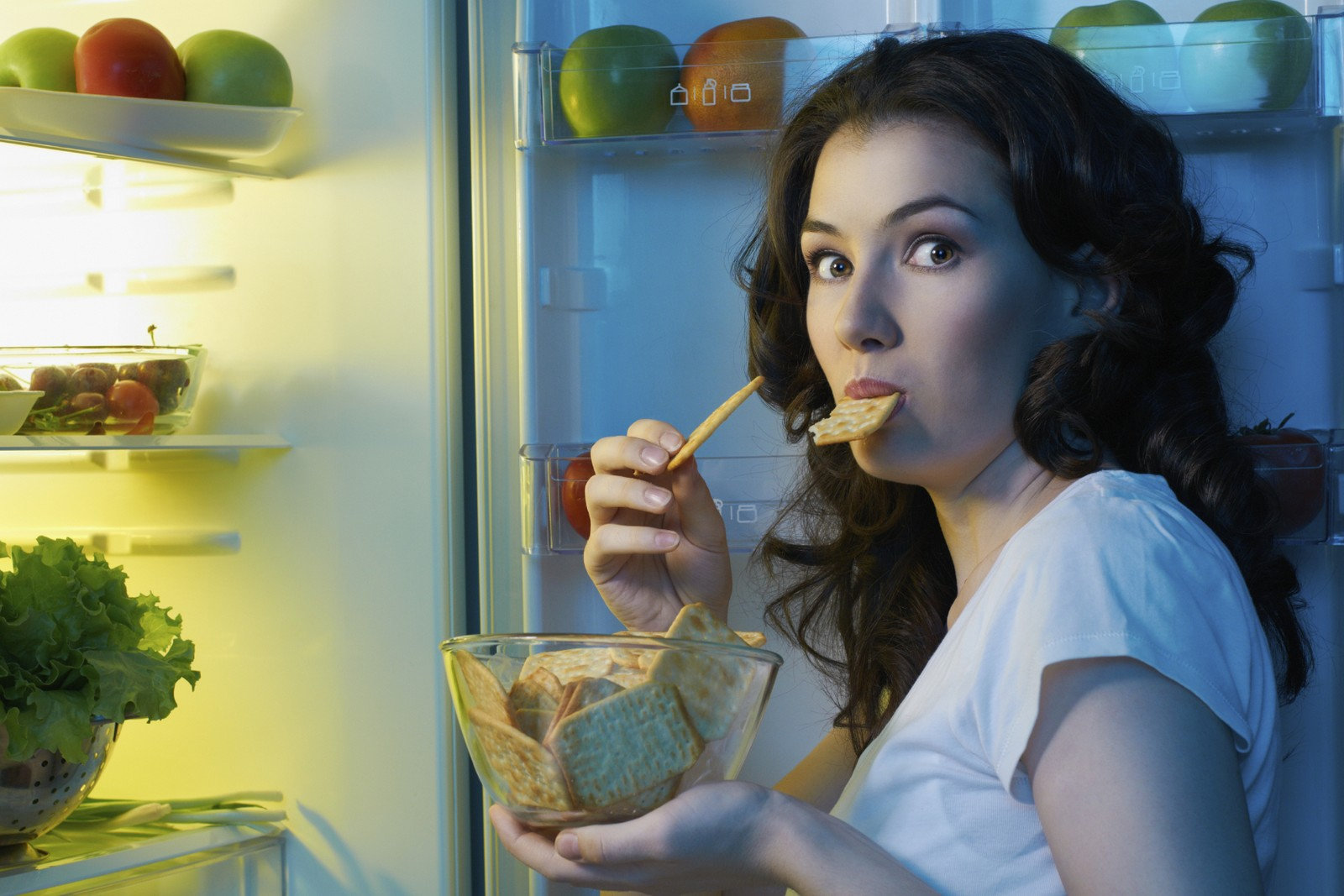 A girl with open refrigerator, eating in night