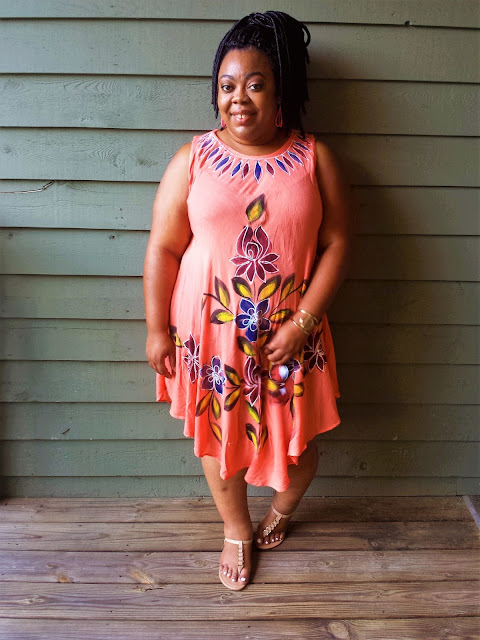 Body positive blogger in sundress, sandals, faux locs and a smile.