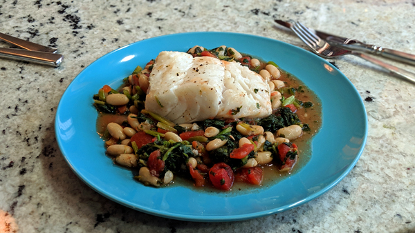 image of a piece of cod sitting atop a mix of cooked vegetables on a plate, which is sitting on my kitchen counter