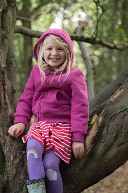 A 5 year old girl in a pinky hoody sits smiling in a tree