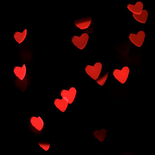 Tiny red hearts juxtaposed against a black background.