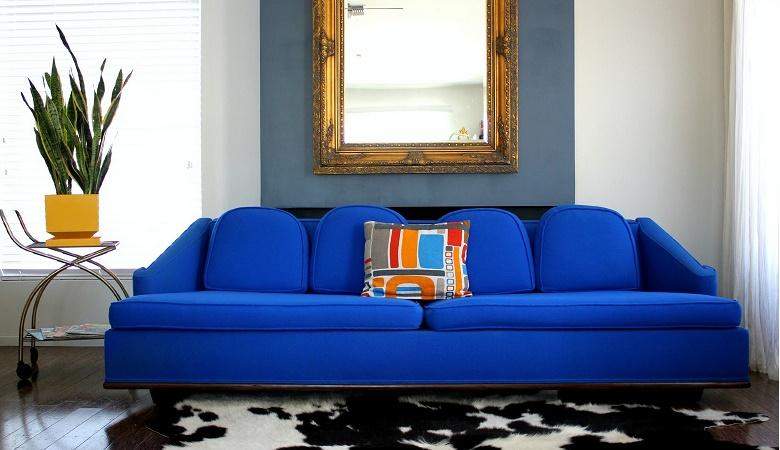 sofá azul com uso de espelho na parede
