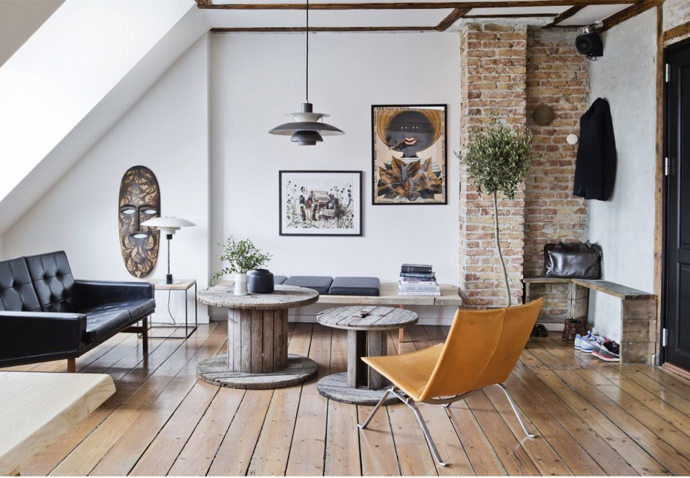 A open space apartment with exposed brick walls, recycled wood and unique  designer furniture in combination with special vintage finds.