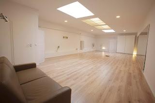 Studio mit weißen Wänden, braunem Boden und Sofa