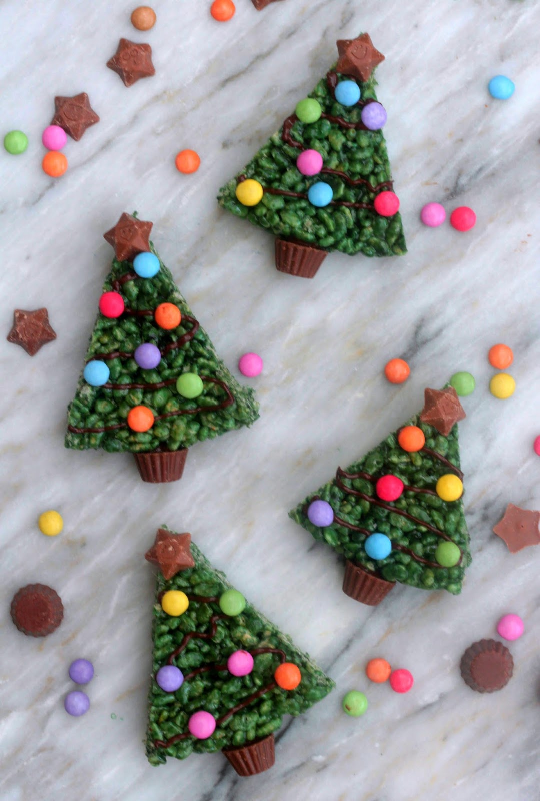 Gently press marshmallows together as you build the tree. Continue this process, making rows of 4, 3, 2 and 1. Add the final marshmallow to the base of the tree. Keep excess chocolate. Place in the freezer for 10 minutes. Take marshmallow Christmas tree out of the freezer and peel off baking paper.
