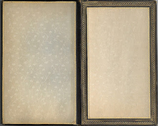 Flyleaf and paste down of book. hey are a pale cream colted silk with a floral pattern.