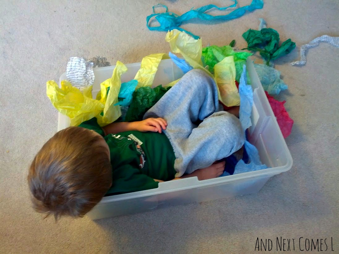 J sitting in tissue paper sensory bin from And Next Comes L