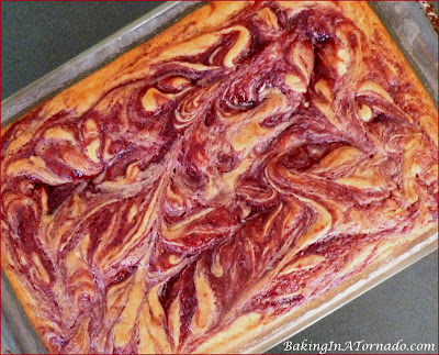 Raspberry Swirl Halloween Cake, a moist white raspberry swirled cake with fluffy vanilla frosting, decorated for Halloween | Recipe developed by www.BakingInATornado.com | #recipe #cake #Halloween