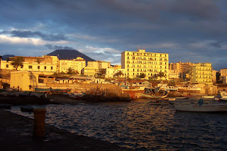 Torre del Greco illuminated by the setting sun with Vesuvius in the background