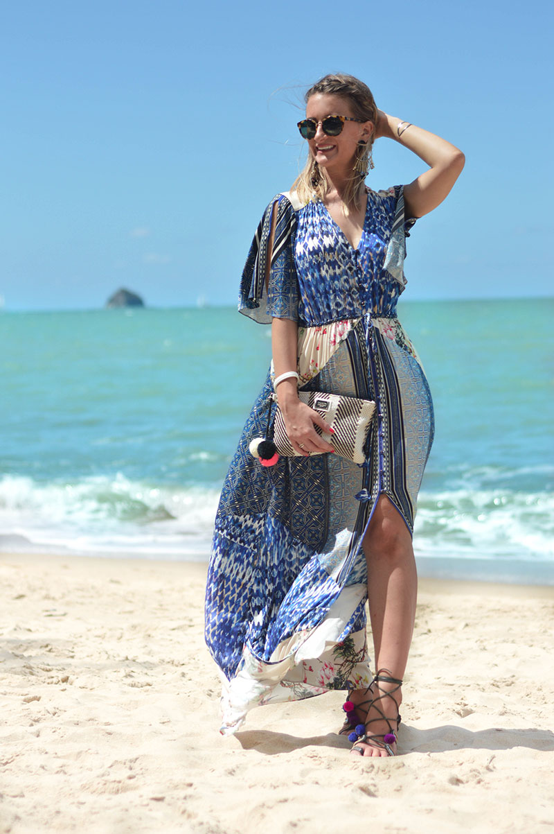 summer holiday vacation outfit blue boho printed split maxi dress with statement earrings and clutch bag