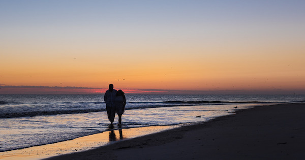 Pareja camina por playa bajo atardecer