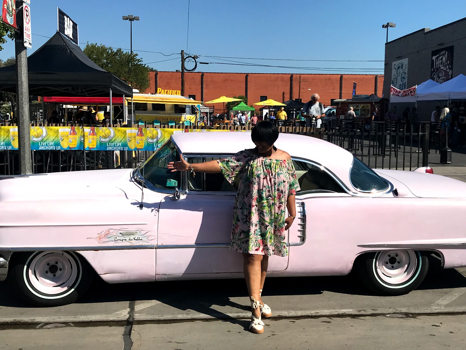 Image: Woman standing in front of pink car showing off her summer dress.
