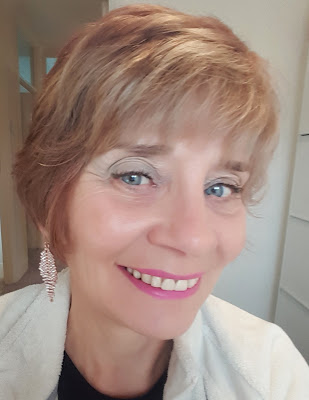 Image shwing a woman over 40 with a full face of makeup including pink lipstick and light green eyshadow