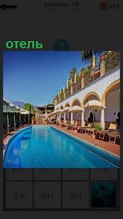 небольшой бассейн в отеле с шезлонгами и номерами