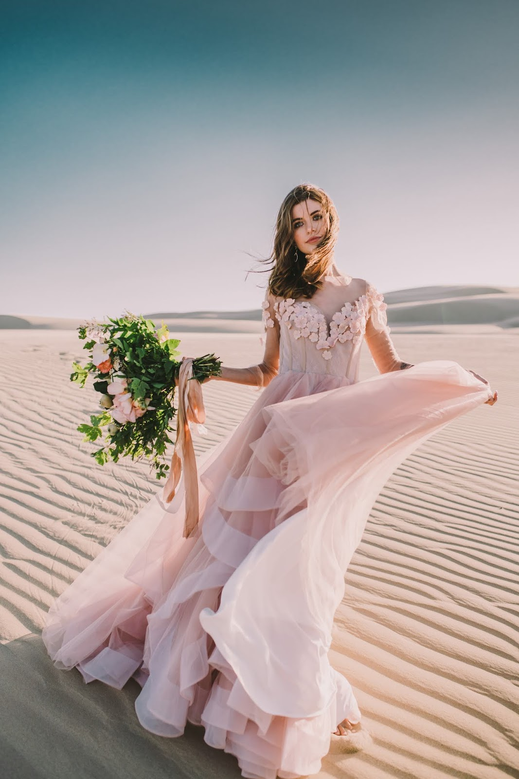 This gorgeous blush pink ballgown is available in multiple colors, it's one of many affordable wedding dresses we have available.